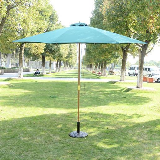 sombrilla estándar verde abierta en medio de zona ajardinada